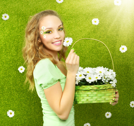 faceart: Smiling girl with a basket of flowers on a green  Stock Photo