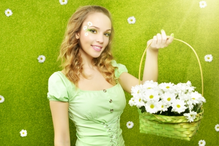 Smiling girl with a basket of flowers on a green background photo