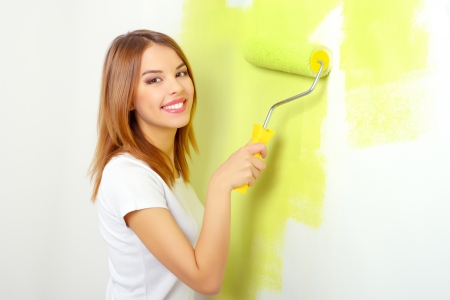 Beautiful girl painting a wall. light background photo