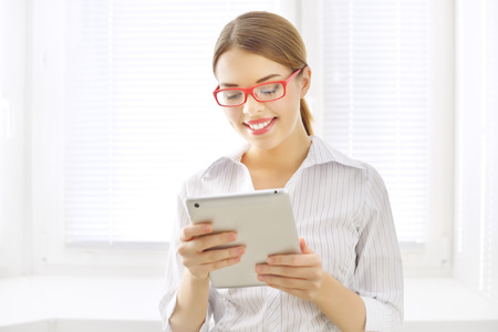 Young business woman with tablet pc on light  Stock Photo - 26038984