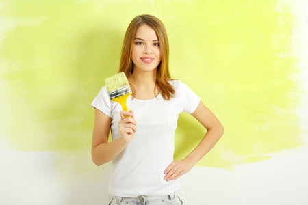 Beautiful girl painting a wall Stock Photo - 26039047