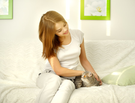 Girl with cat on light wall photo