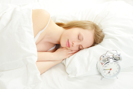 woman lying in bed: Sleeping Girl on the bed. on light background