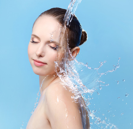 clear skin: Beautiful girl and stream of water on blue