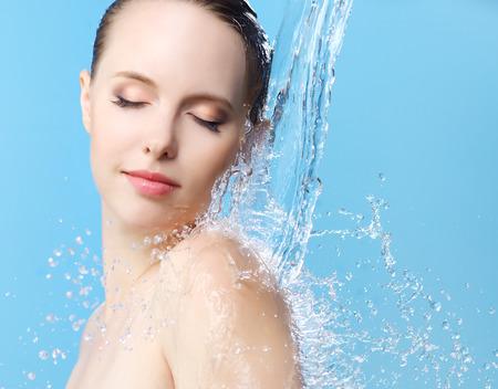 Muchacha hermosa y corriente de agua en azul