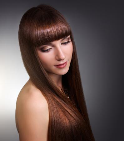 cabello lacio: Hermosa chica con el pelo largo y recto sobre fondo gris Foto de archivo