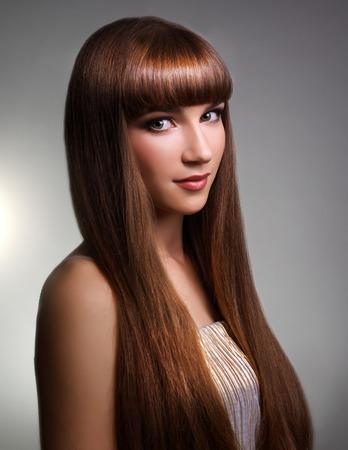 cabello lacio: Hermosa chica con el pelo largo y recto en el fondo gris
