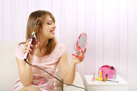 curling irons: Hair curling. Girl in a dress on light background