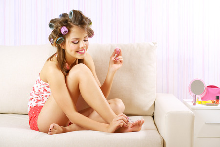 curlers: young woman painting her nails on light background Stock Photo