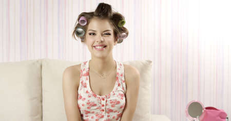 curlers: Retro style. Funny girl with hairstyle on light background