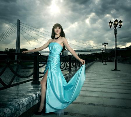 vestido de noche: Chica atractiva en vestido de noche largo. fondo negro
