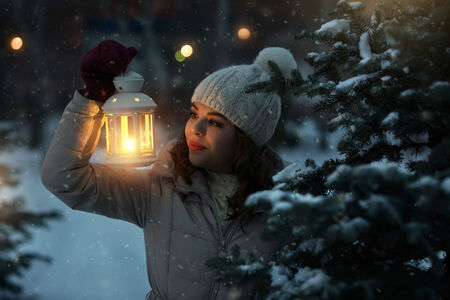 Cute girl with a lantern on dark background photo