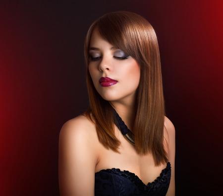 cabello corto: Hermosa chica con el pelo liso sobre fondo oscuro