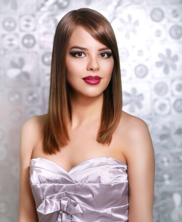 smooth hair: Beautiful girl with straight hair on gray background