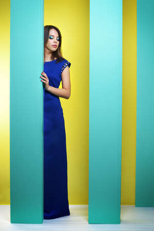 Attractive girl in a long dress on an abstract background photo