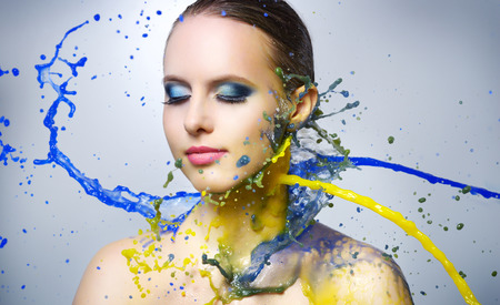 face paint: Beautiful girl and colorful paint splashes on light background