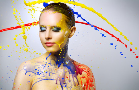 Beautiful girl and colorful paint splashes on light background