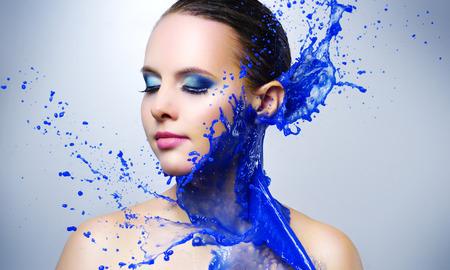 Beautiful girl and blue paint splashes on light background Stock Photo