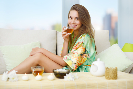An attractive girl with a cup of tea on a light background