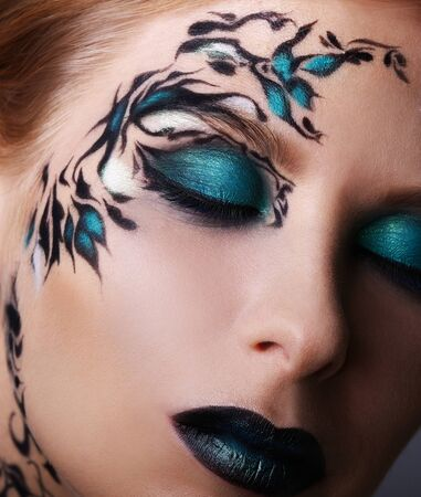 faceart: Beautiful face of a woman with creative make-up Stock Photo