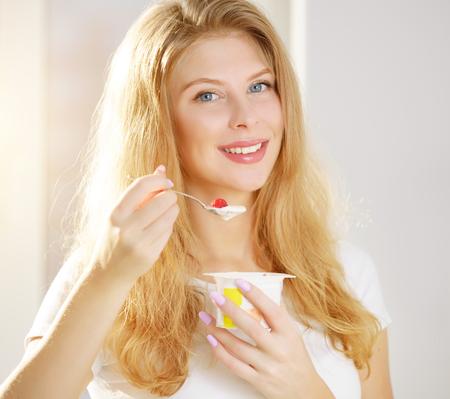 niña comiendo: Mujer joven que come el yogur en casa