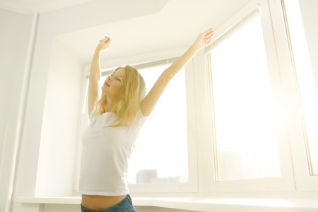 wellness sleepy: Girl stretching in the morning. Young girl waking up in the morning. background window