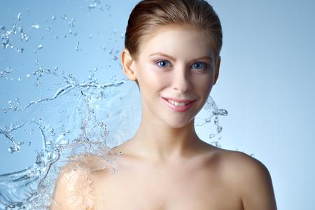 Soin de la peau. Belle fille et flux d'eau sur fond bleu
