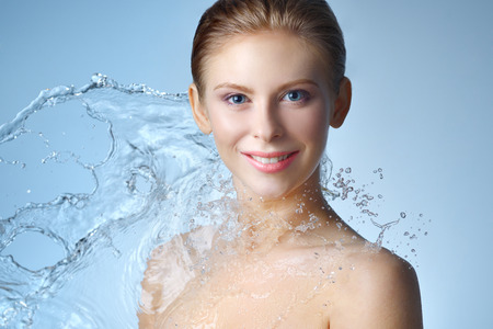 Beautiful girl and stream of water on blue background Foto de archivo