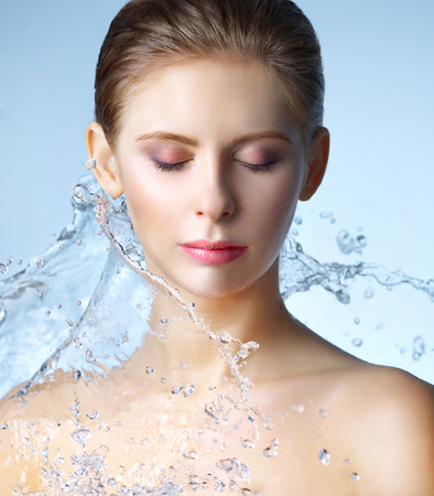 Beautiful girl and stream of water on blue background Reklamní fotografie