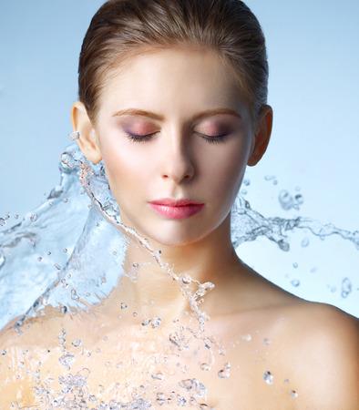 Muchacha hermosa y chorro de agua sobre fondo azul Foto de archivo