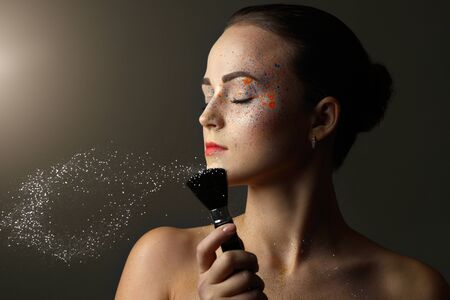faceart: Young woman with make-up brush. black background Stock Photo