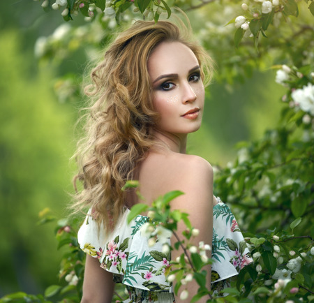 Girl with a beautiful make-up. Flowering Apple Tree photo