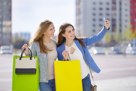 Two stylish girls with shopping bags. Outdoors photo