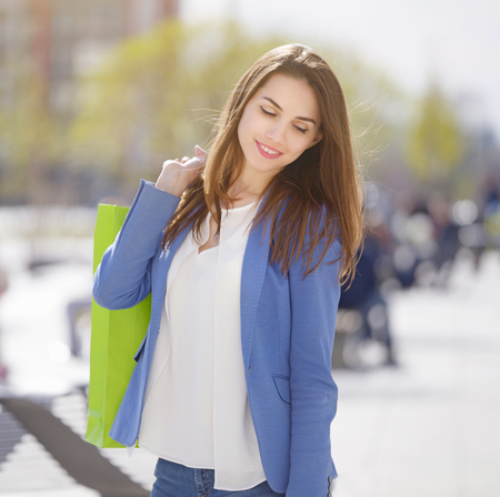 Smiling girl with shopping bags. Outdoors photo