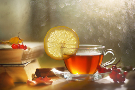 A cup of tea with lemon. Autumn leaves