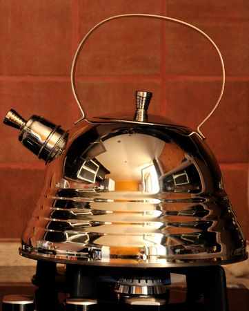 a stainless steel kettle with whistle siting on a stove and reflecting a kitchen   photo
