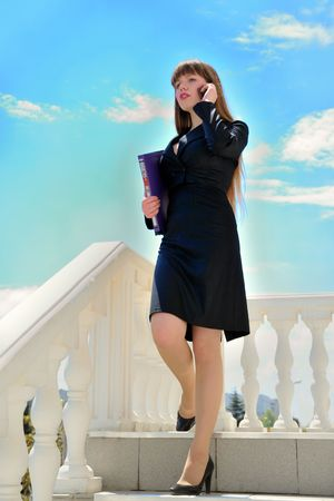 Beautiful young business woman is going downstairs and talking by mobile phone Stock Photo - 4836298