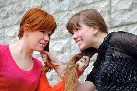 Two beautiful sisters pull each others hair photo