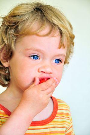 fair haired: Little fair haired girl eating strawberry  Stock Photo