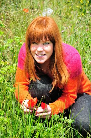 redheaded girl is sitting on a meadow, she has found spring flowers, she is happy Stock Photo - 5045257