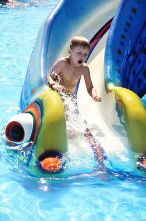 Cute little boy sliding down a water slide Stock Photo