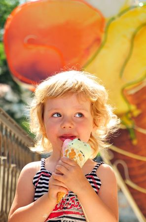 little girl outdoors eating huge ice cream cone photo