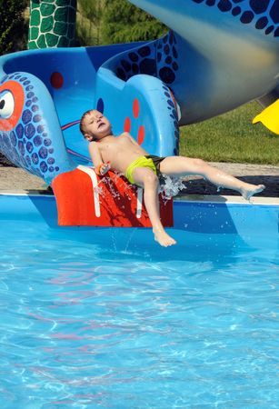 Cute and funny  little boy sliding down a water slide photo