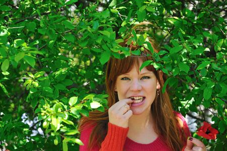 tenager: redhaired beautiful girl eats green plum Stock Photo