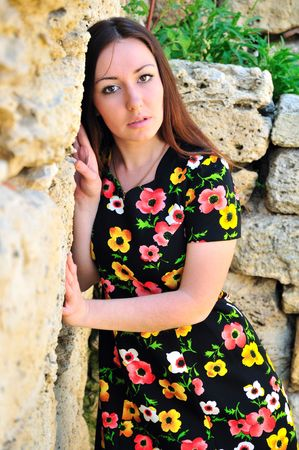 beautiful brunette standing close to the ancient stone wall, she is wearing flowered dress photo