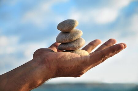 rende: balancing stones  in mans palm over blue sky
