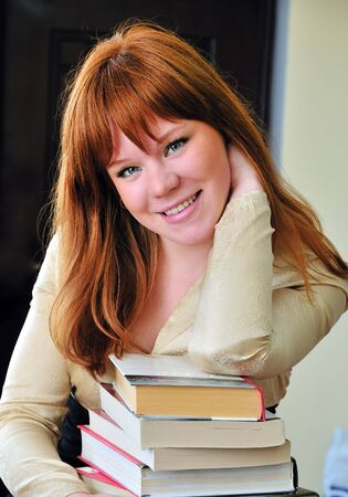 clever and beautiful redheaded girl is going to pass an exam, so she has to read a lot of books Stock Photo