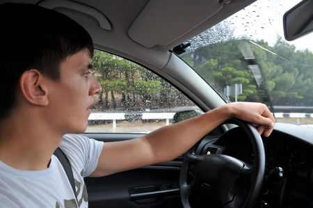 man should be careful, he drive his car on a wet road, it is greasy  photo