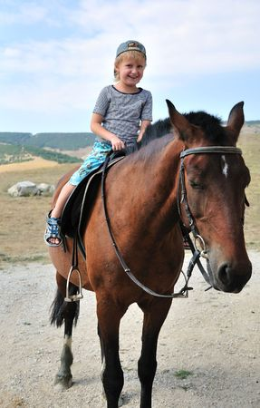 little boy is riding horse, its his the first time!