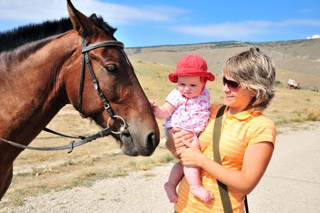mother habituating her little daughter with horse Stock Photo - 5440538
